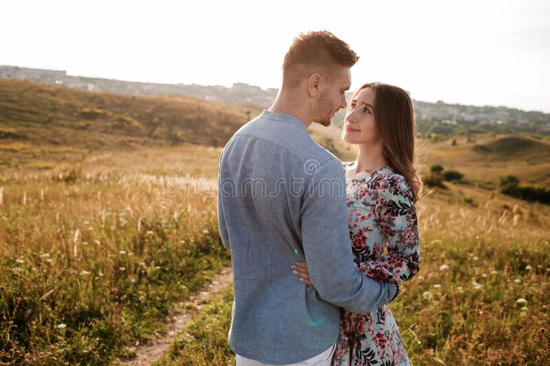 Hugging couple smiling and looking at each other, side view. the origin of love.  royalty free stock photos