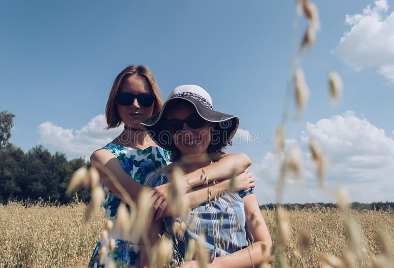 Hugging female friends standing in oat field stock images