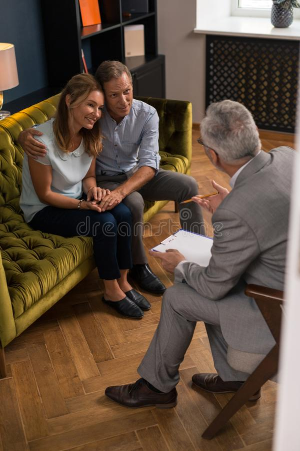 Hugging husband and wife sitting on the sofa stock photos