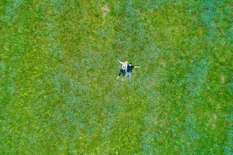 The hugging loving couple is lying on the meadow with their lovely dog. The handsome man is touching the cheek of his beautiful by royalty free stock images