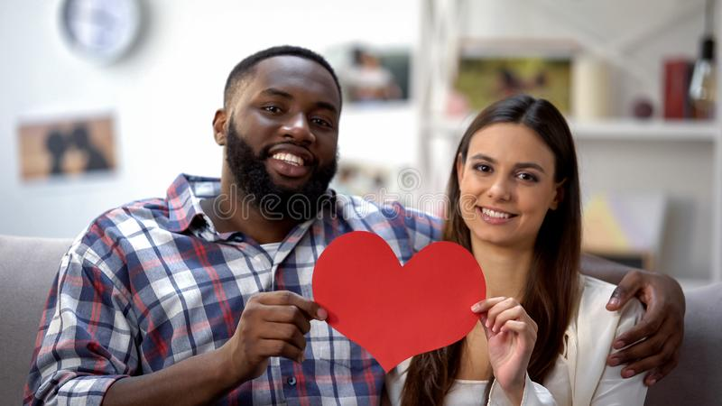 Hugging mixed-race couple showing paper heart to camera, sitting on sofa at home royalty free stock image