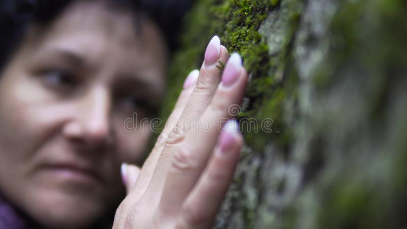Woman laying on a rock. Hugging a nature. A woman puts her arms around large stone with moss, exchanging emotions and charging energy from nature royalty free stock images