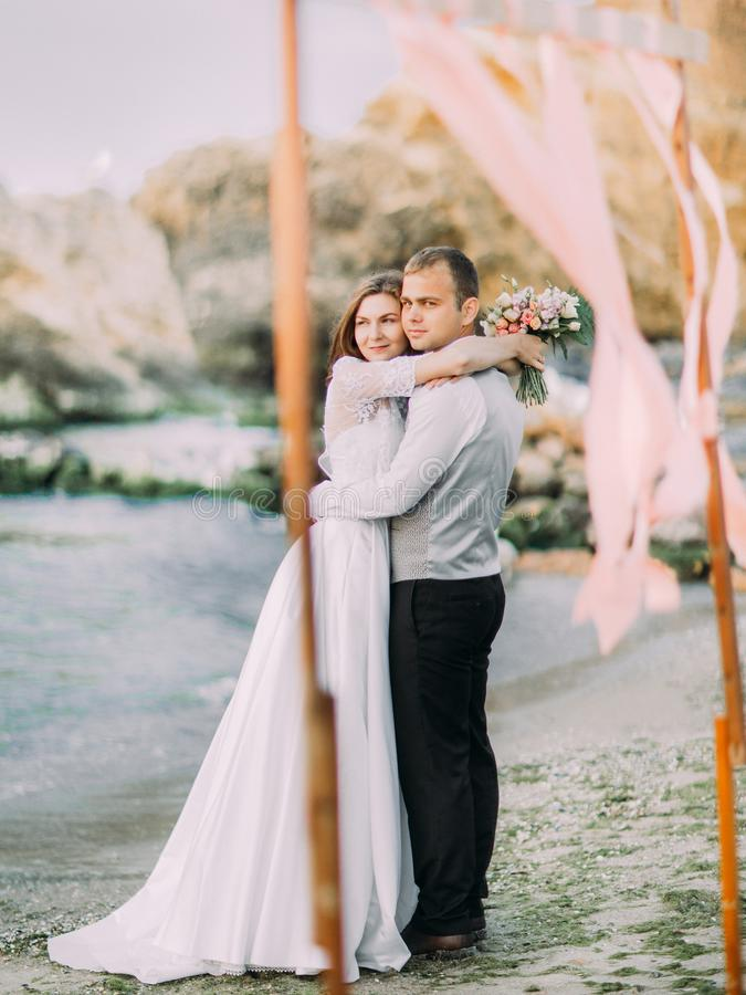 Hugging newlywed couple in the sea during the sunset. Hugging newlywed couple in the sea during the sunset stock image