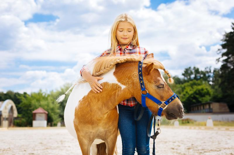 Caring pleasant girl hugging little cute pony with braid royalty free stock photography