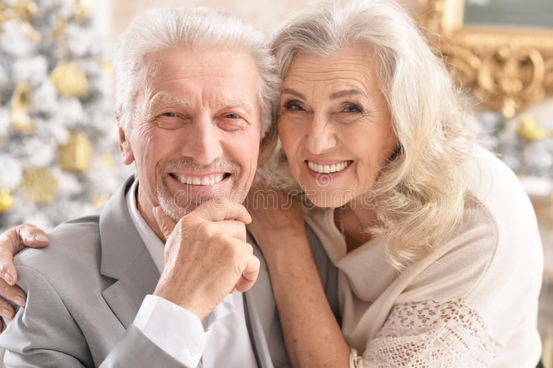 Hugging senior couple with blurred Christmas decorations royalty free stock photography