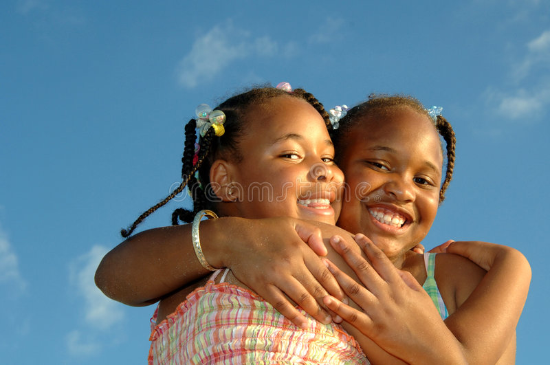 Hugging sisters. Two african american sisters hugging against a blue sky