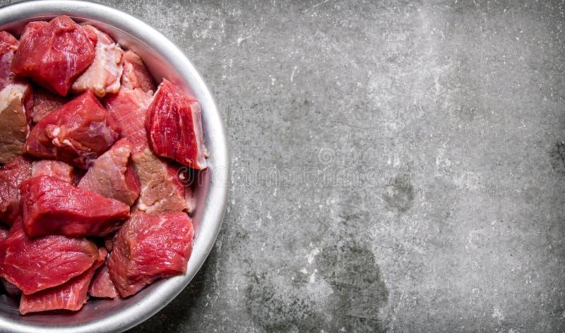 Huggit av rått kött i en kopp På stentabellen royaltyfri fotografi