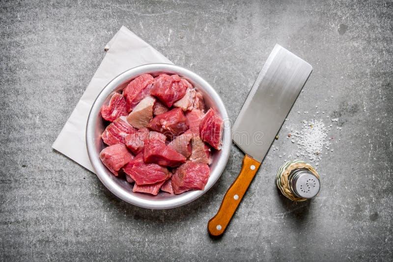 Huggit av rått kött med en slaktarekniv och saltar arkivfoton
