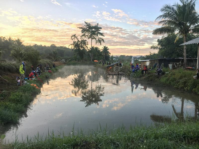HUGGTAND CHIANG MAI /THAILAND - DECEMBER 22,2018: Fiskare fångar fisken på sjön i morgonen med härlig himmel fotografering för bildbyråer