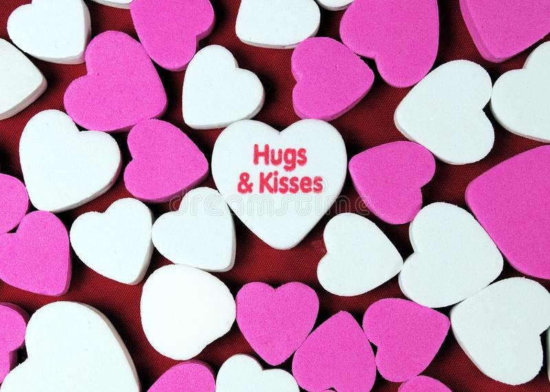 Hugs and Kisses. Pink and white hearts with hugs and kisses stock photos