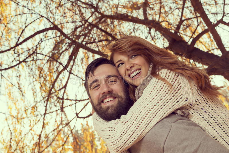 Hugs, kisses and love in autumn. Couple in love having fun and fooling around on a wonderful autumn day in a park, guy piggybacking his girlfriend royalty free stock photography