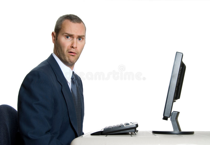 Huh?. Surprised man in blue suit in front of computer royalty free stock images