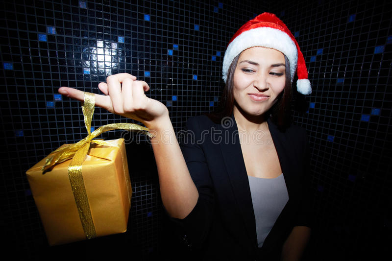 Huh. Portrait of young businesswoman in Santa cap holding Chistmas gift and looking at it with sneer stock photo