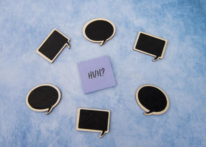Huh written on note paper surrounded by speech bubbles. On a blue background royalty free stock images