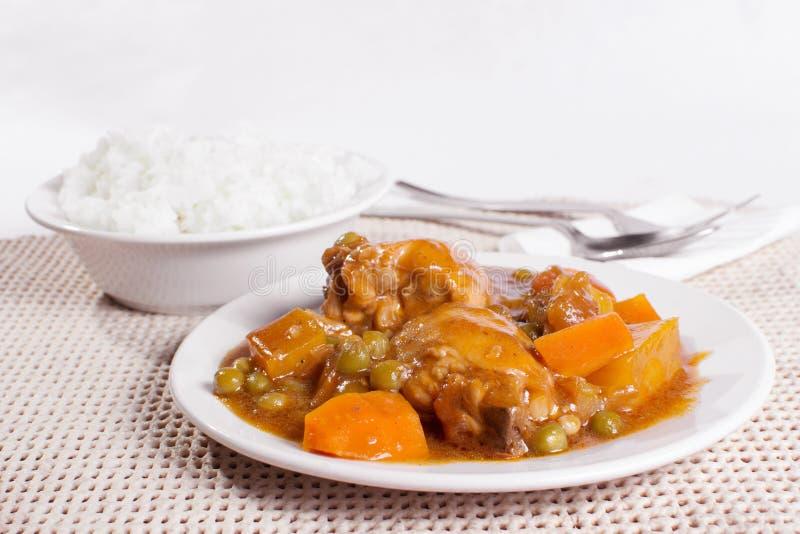 Huhn afritada mit Schüssel Reis lizenzfreie stockbilder