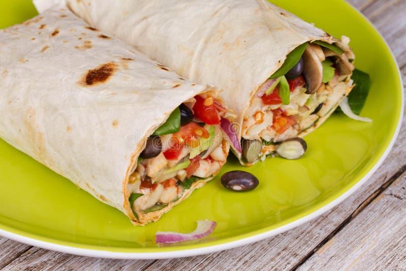 Huhn, Avocado und schwarze Bohnen Burrito in der grünen Platte lizenzfreie stockfotos