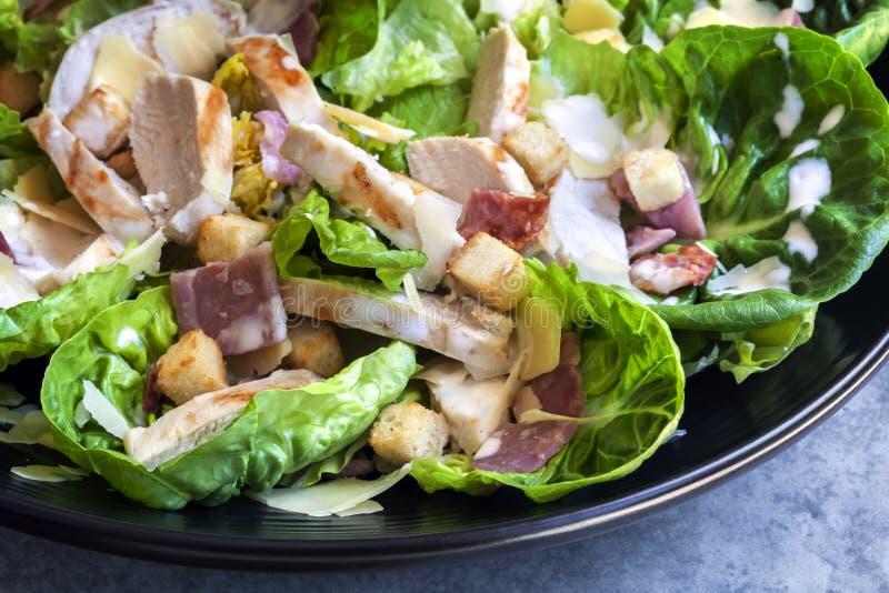 Huhn Caesar Salad in der schwarzen Schüssel stockfotos