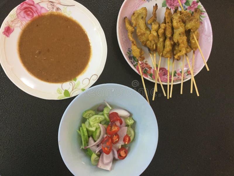 Huhn Satay mit Erdnuss-Soße und würzigem Gurken-Salat stockbilder