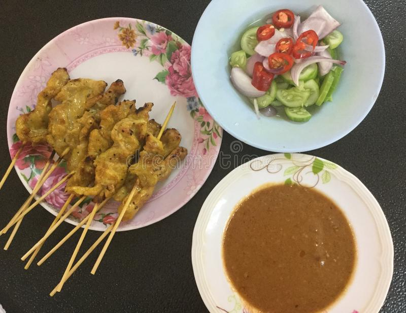 Huhn Satay mit Erdnuss-Soße und würzigem Gurken-Salat stockfotografie