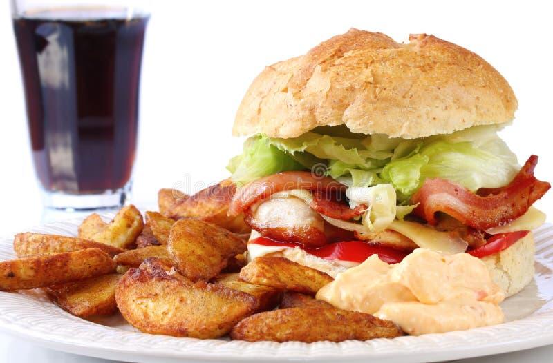 Huhn und Speck-Burger und Keile stockfotos