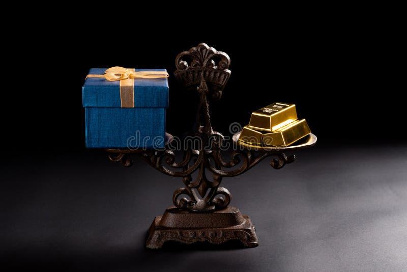Huidige doos en goudstaven op evenwichtige schaal royalty-vrije stock foto