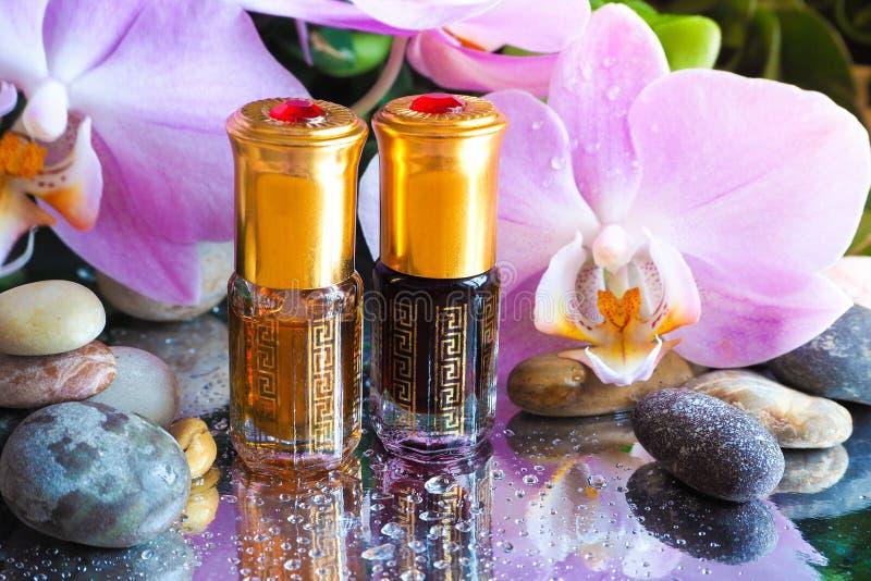 Huile arabe de massage Les pierres et l'orchidée fleurissent avec de l'huile naturelle dans le salon de station thermale photographie stock