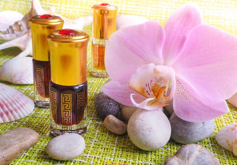 Huile arabe de massage Les pierres et l'orchidée fleurissent avec de l'huile naturelle dans le salon de station thermale photo libre de droits