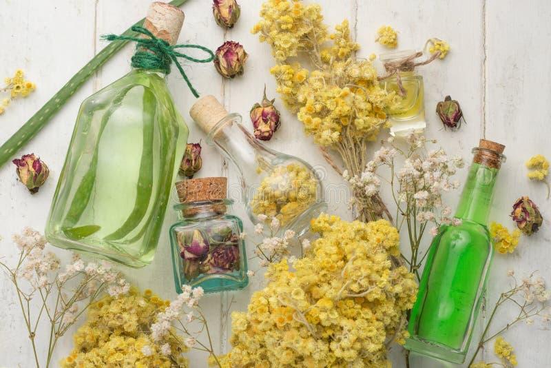Huile aromatique, herbes aromatiques dans des bouteilles en verre, sur un fond en bois Le concept du soin et de la beauté de corp photos libres de droits
