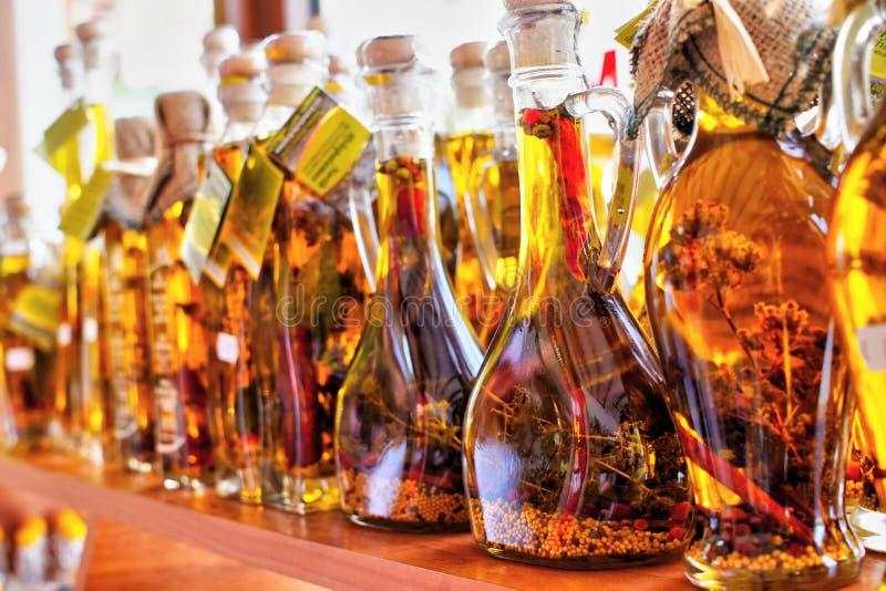 Huile d'olive d'or avec des épices dans des bouteilles en Grèce images stock