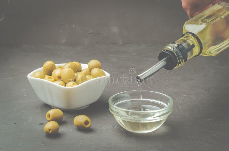 Huile d'olive coulant de la bouteille dans le bol et les olives fraîches dans la plaque en céramique et sur la table en pierre no photo stock