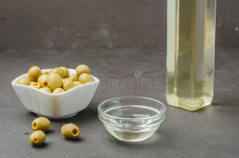 Huile d'olive coulant de la bouteille dans le bol et olives fraîches dans la plaque en céramique image stock