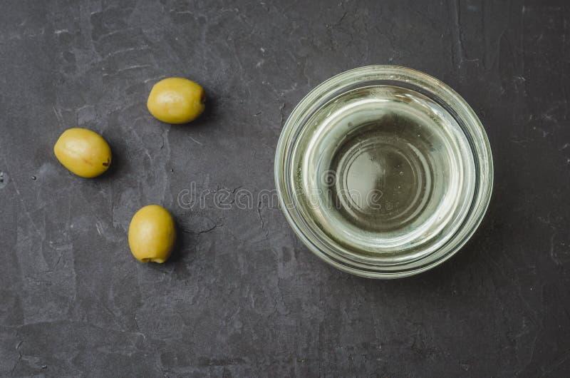 Huile d'olive qui déverse dans le bol et les olives fraîches sur fond de pierre noire Vue supérieure image stock