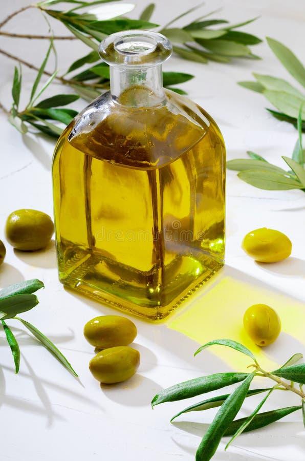 Huile d'olive vierge supplémentaire dans la bouteille en verre foreground Inclut des feuilles et des branches d'olivier photo stock