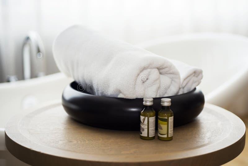 Huile de bain blanche de serviette et de massage sur la table dans la salle de bains image libre de droits