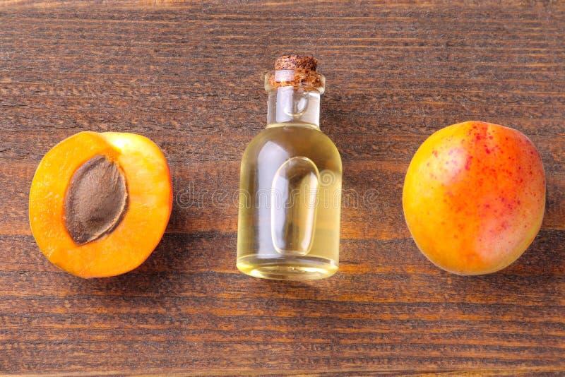 Huile de graines d'abricot à côté des abricots frais sur un fond en bois brun images stock