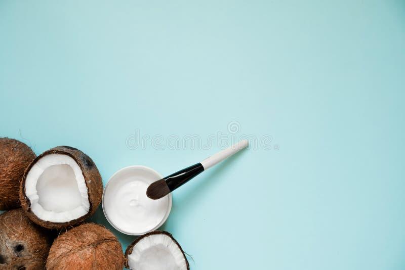 Huile de noix de coco fraîche dans la verrerie et la cuillère en bois sur le fond de table de couleur images stock