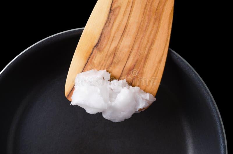Huile de noix de coco sur la spatule en bois au-dessus de la casserole enduite photo libre de droits