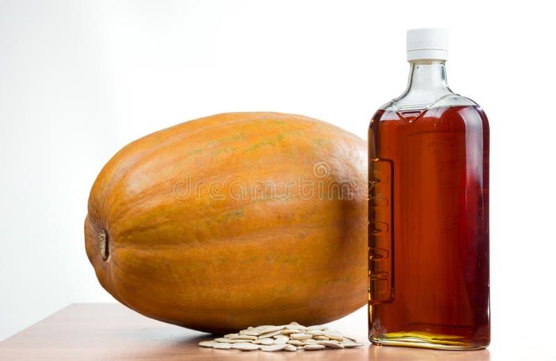 Huile de potiron dans une bouteille, potiron, graines de citrouille photos libres de droits