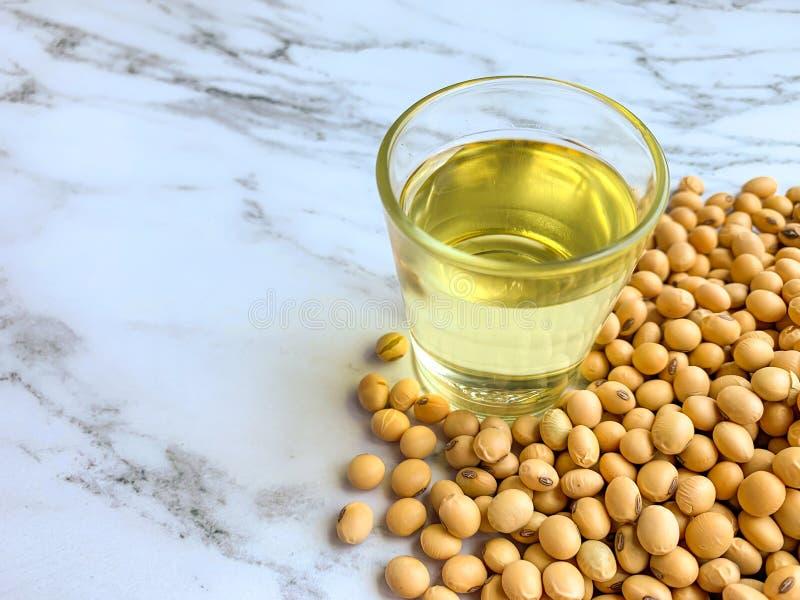 Huile de soja dans un verre placé près de la pile de graine de soja sur un fond de marbre blanc photo libre de droits