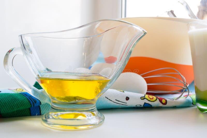 Huile de tournesol dans un graisseur transparent de verre sur un rebord de fenêtre blanc à côté des ingrédients pour des crêpes images stock