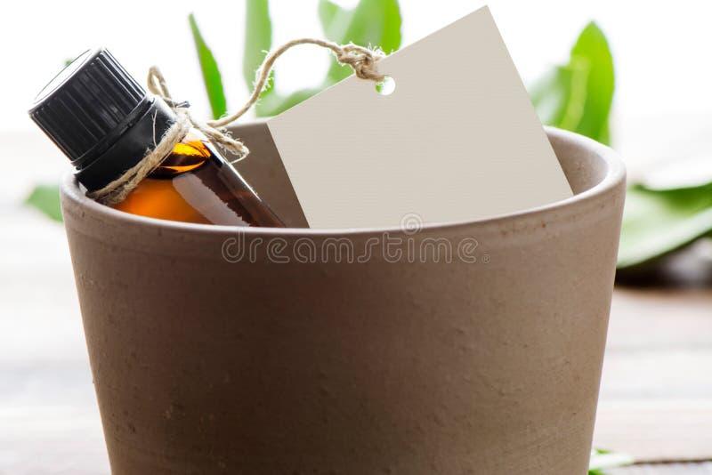 Huile essentielle, étiquettes vides, dans un pot d'argile photo stock