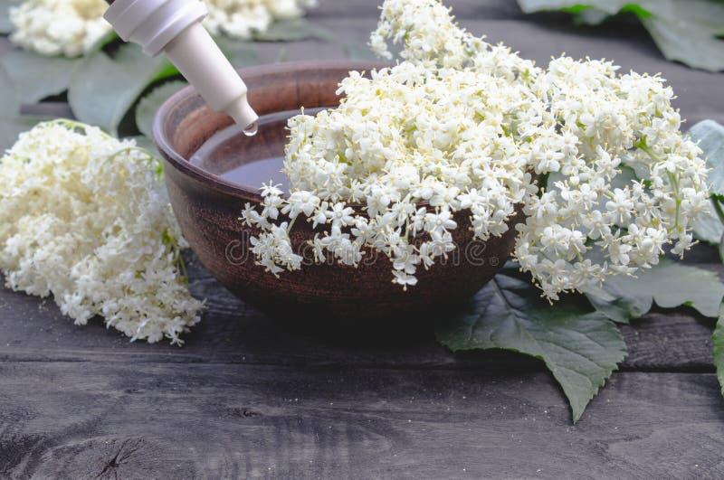 Huile essentielle de baie de sureau ou extrait de la teinture avec des fleurs de baie de sureau sur un fond en bois images stock