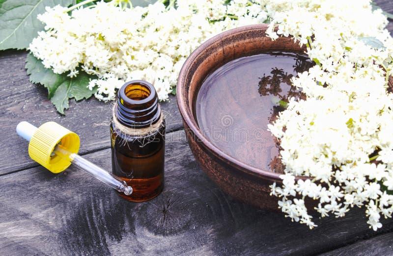 Huile essentielle de baie de sureau ou extrait de la teinture avec des fleurs de baie de sureau sur un fond en bois image libre de droits