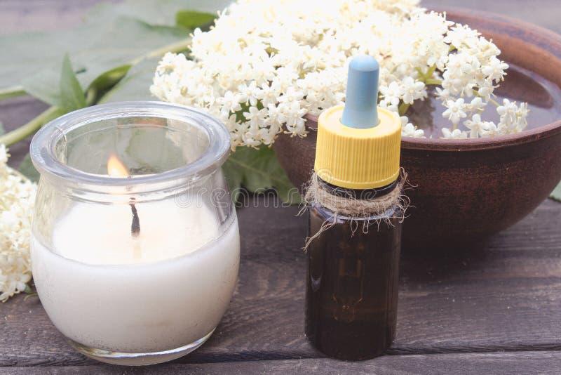 Huile essentielle de baie de sureau ou extrait de la teinture avec des fleurs de baie de sureau sur un fond en bois photographie stock