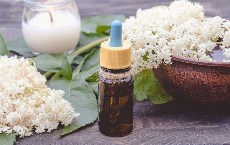 Huile essentielle de baie de sureau ou extrait de la teinture avec des fleurs de baie de sureau sur un fond en bois photo stock