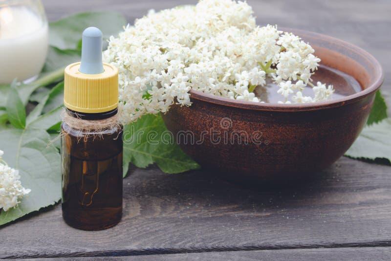 Huile essentielle de baie de sureau ou extrait de la teinture avec des fleurs de baie de sureau sur un fond en bois photos stock