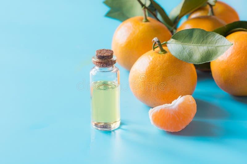 Huile essentielle de mandarine dans la bouteille en verre au-dessus du fond bleu en pastel Concept de Skincare photos libres de droits