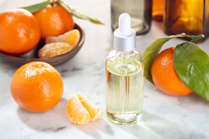 Huile essentielle de mandarine Huile de mandarine sur la bouteille en verre avec le compte-gouttes Huile d'agrume images stock