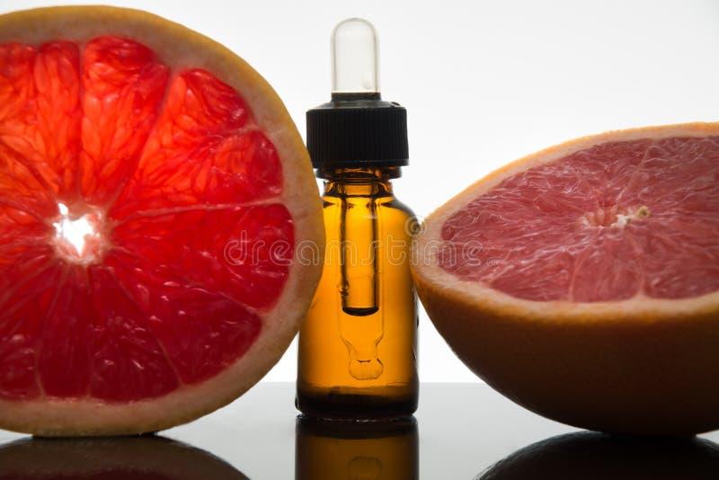 Huile essentielle de pamplemousse, extrait, essence, dans la bouteille ambre avec le compte-gouttes photos stock