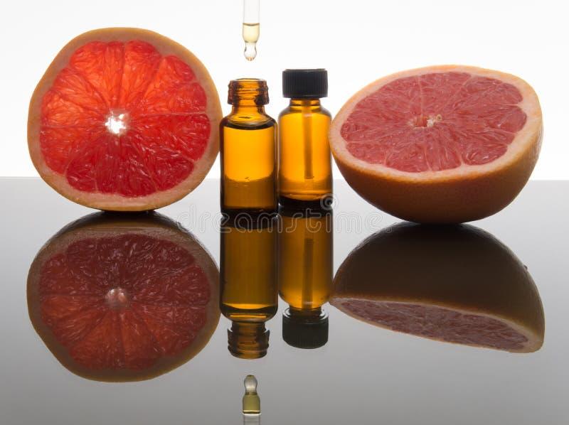 Huile essentielle de pamplemousse, extrait, essence, dans la bouteille ambre avec le compte-gouttes image libre de droits